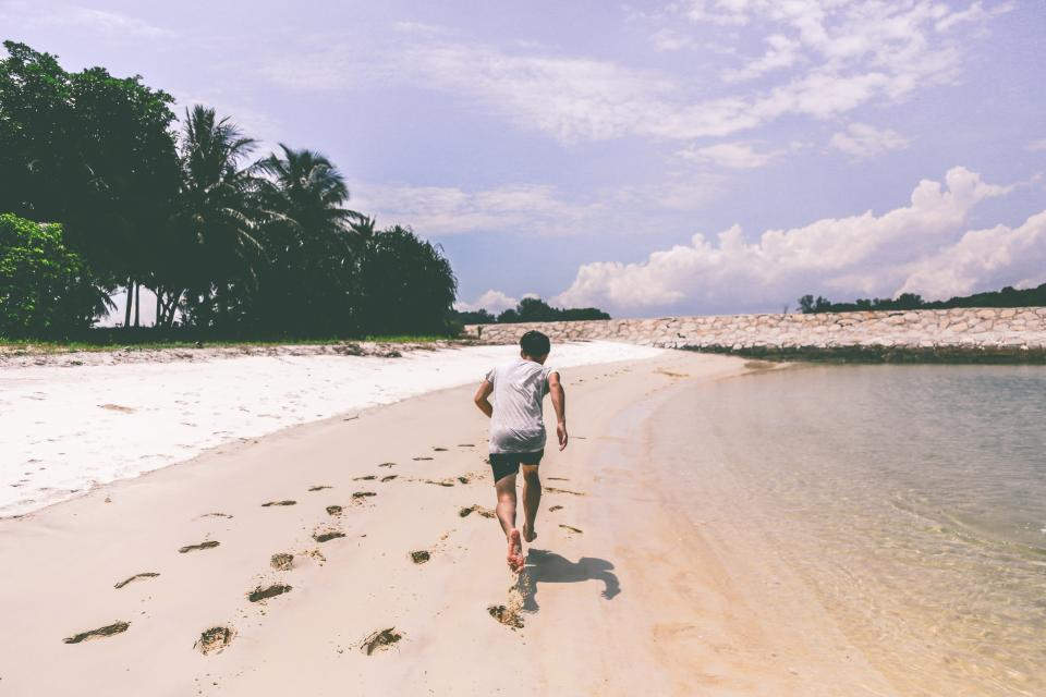 boy guy running beach sand shore footprints fitness exercise shorts tshirt summer sunny palm trees sky people health