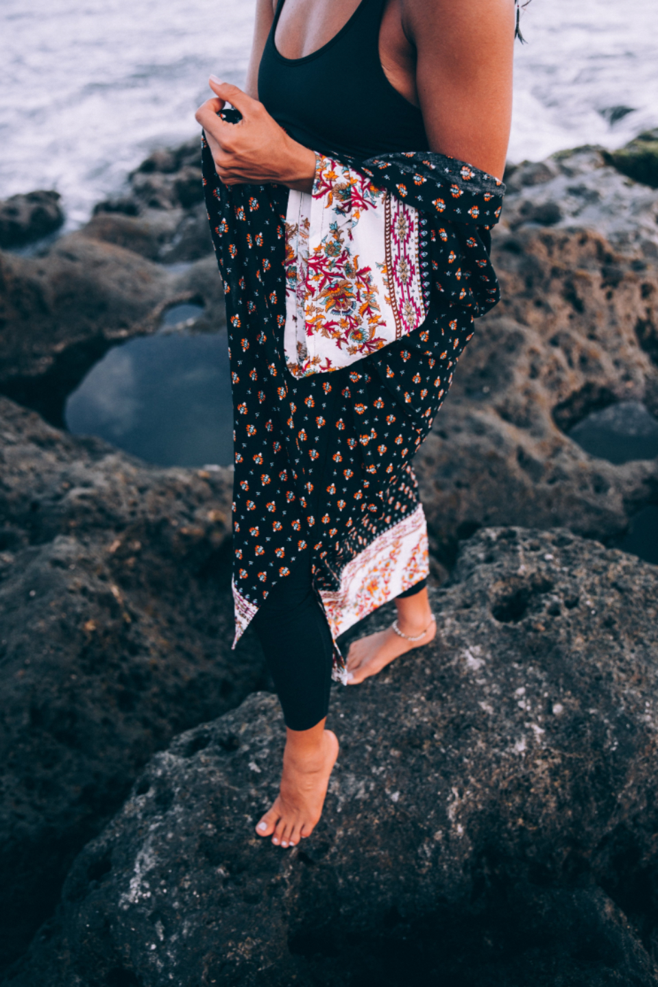 ocean sea person coast shore vacation travel tan robe female woman necklace rocks nature outdoors feet
