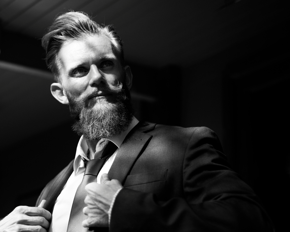 adult man beard boldness business confidence corporate courage outdoors standing style suit sunlight sunny caucasian; black and white