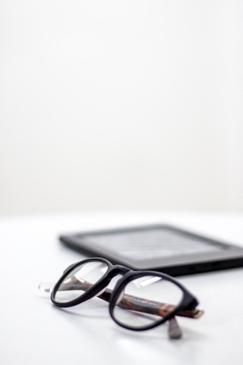 glasses white table tablet reading close up bokeh background copy space eyewear modern nobody object optic vision style