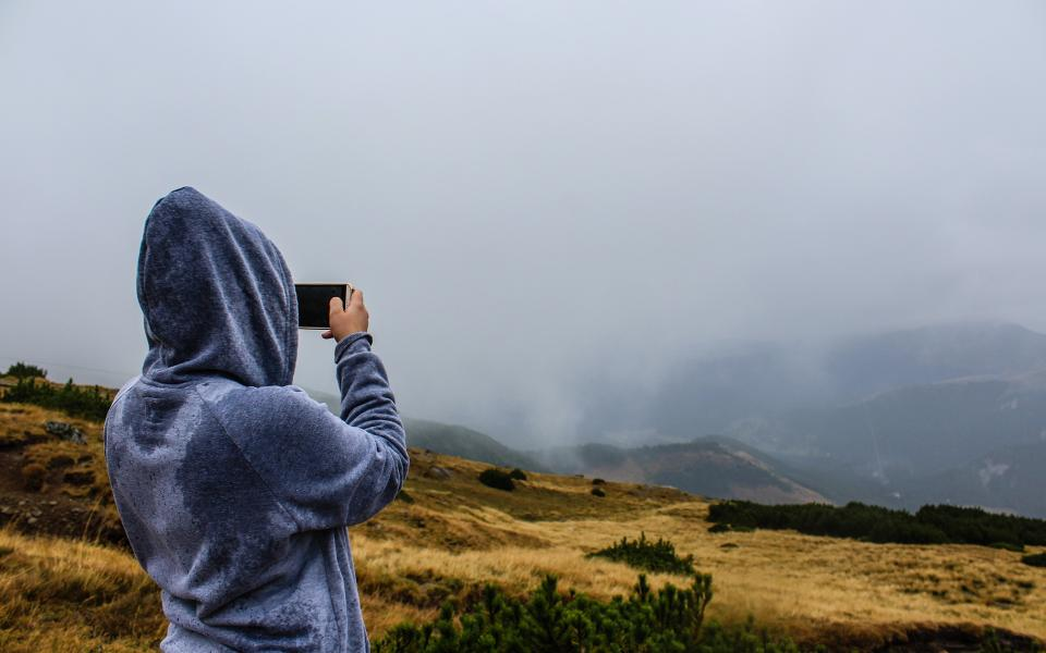 people hoodie outdoors nature adventure fields mountains hills landscape foggy smartphone cell phone picture photography photographer clouds