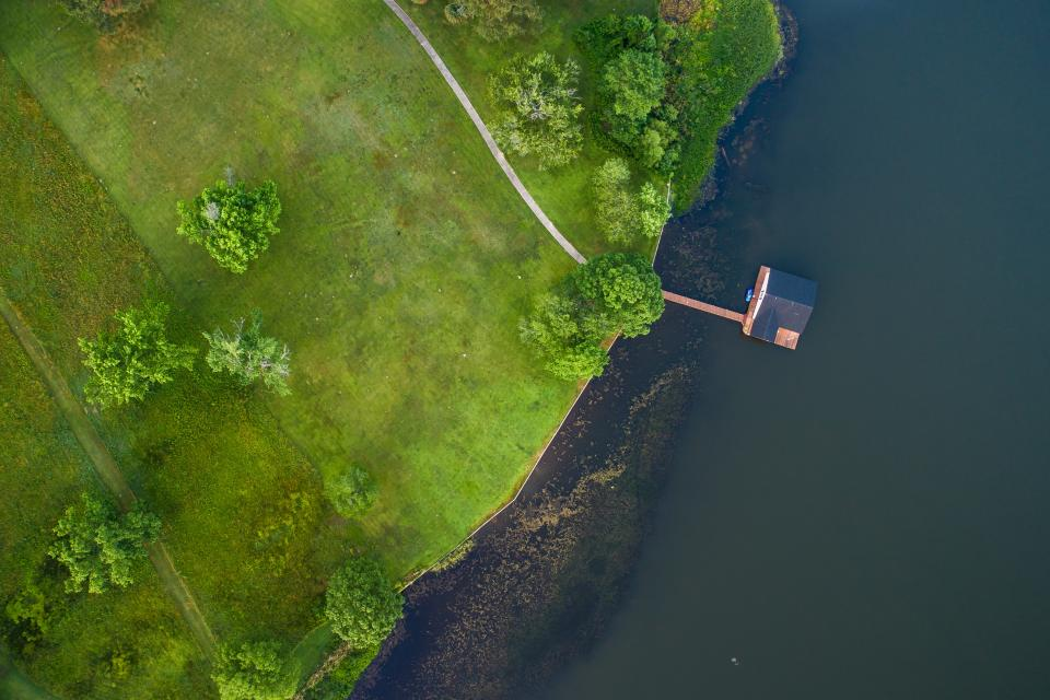 pier ocean sea water green field grass trees plants nature aerial view