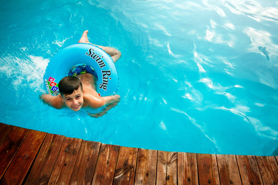 young boy swimming pool water wet child play fun smile wood deck ring lifesaver help