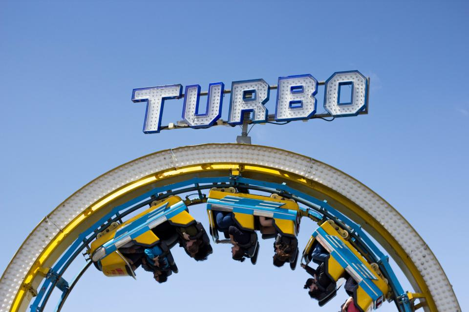 still rides themed park rollercoaster upside down steel signage turbo people customers sky blue friends