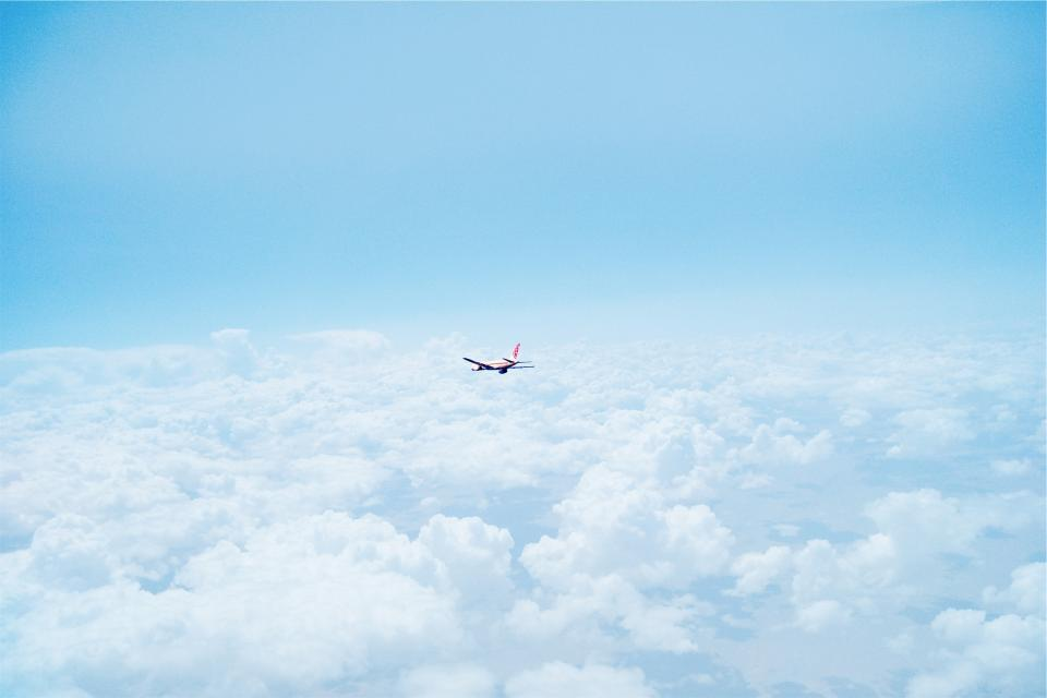 airplane above the clouds sky blue travel transportation flying