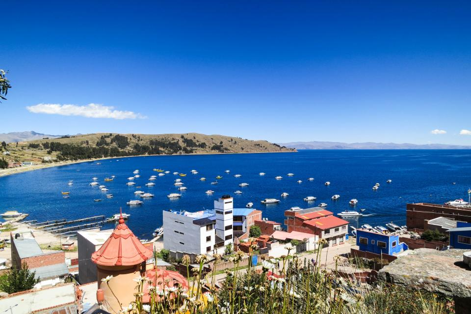 Lake Titicaca Copacabana Bolivia water boats buildings mountains coast sky town