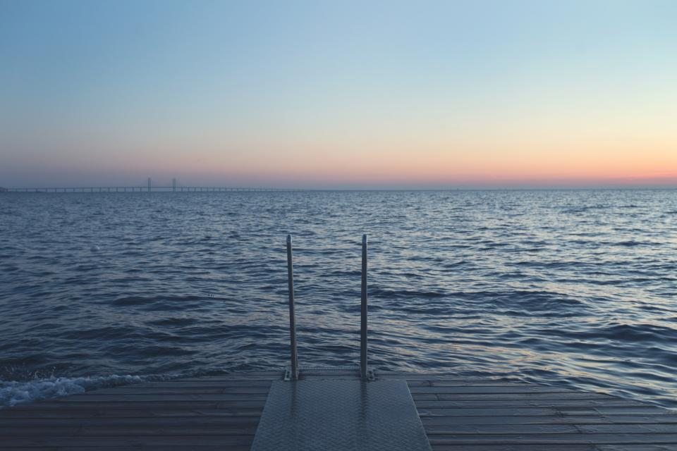 dock ladder lake water waves sunset dusk sky horizon bridge