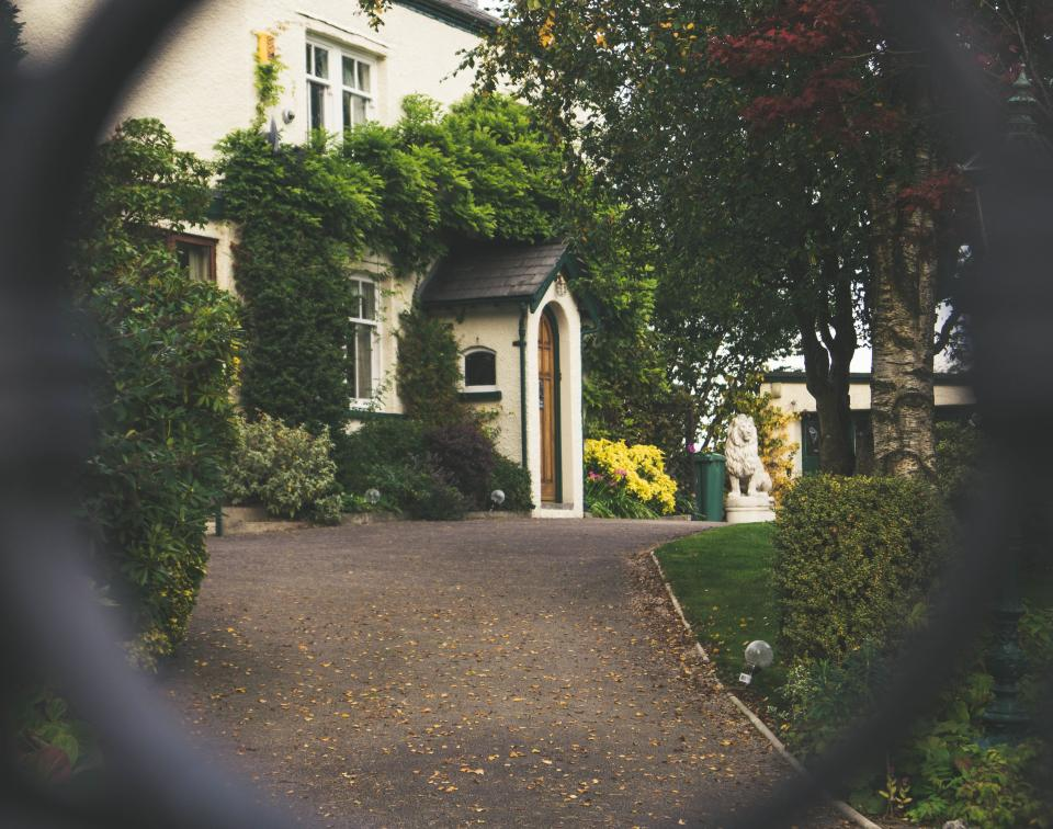 house home residence path road lawn grass trees plants bushes vines windows door statue gate bokeh