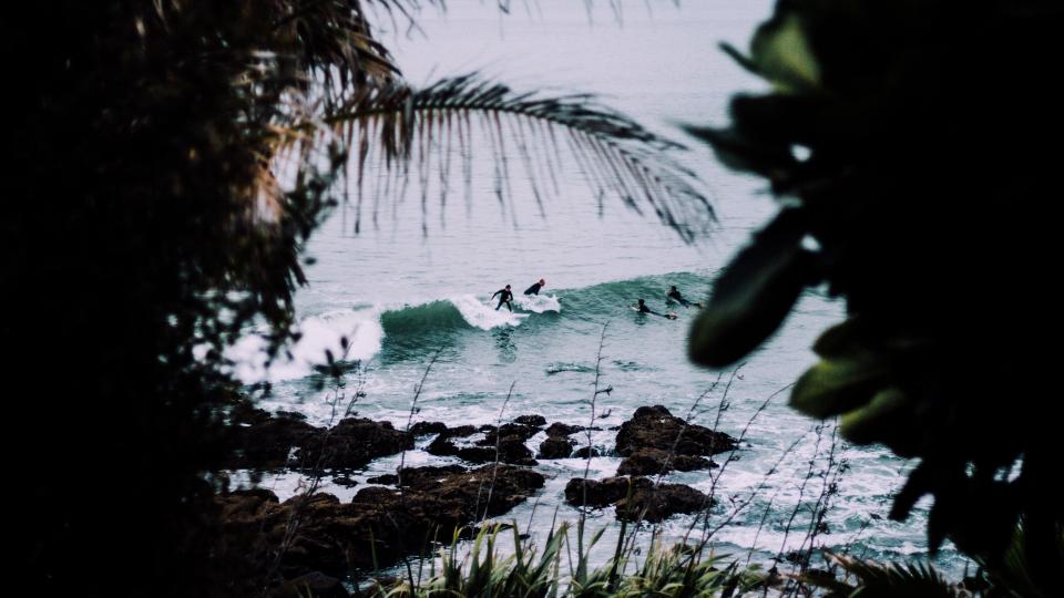 sea ocean water waves nature trees plant rocks coast people swimming sport surfing