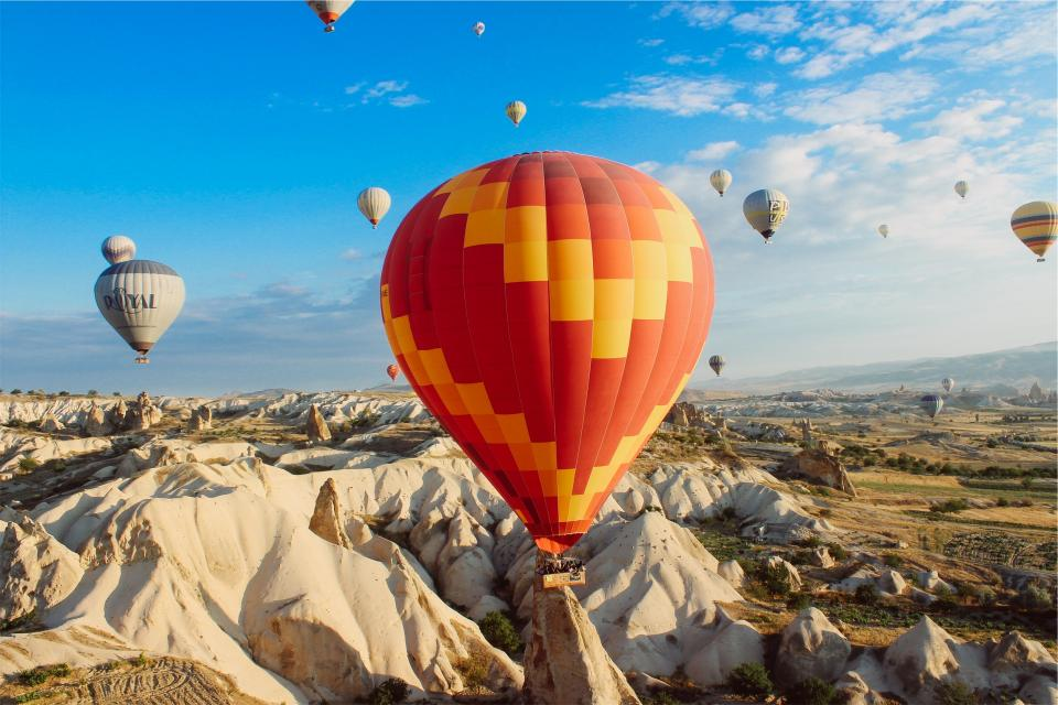 hot air balloons rocks cliffs valleys fields landscape