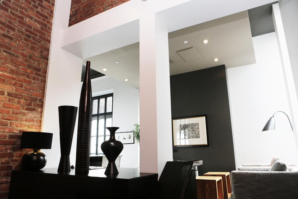 condo loft apartment brick wall furniture lamps couch tables pictures windows lights beams pillars decor indoors