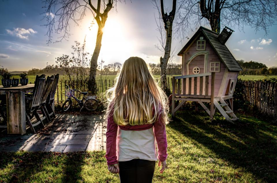 girl child kid daughter people blonde backyard grass field playhouse trees sunshine sky