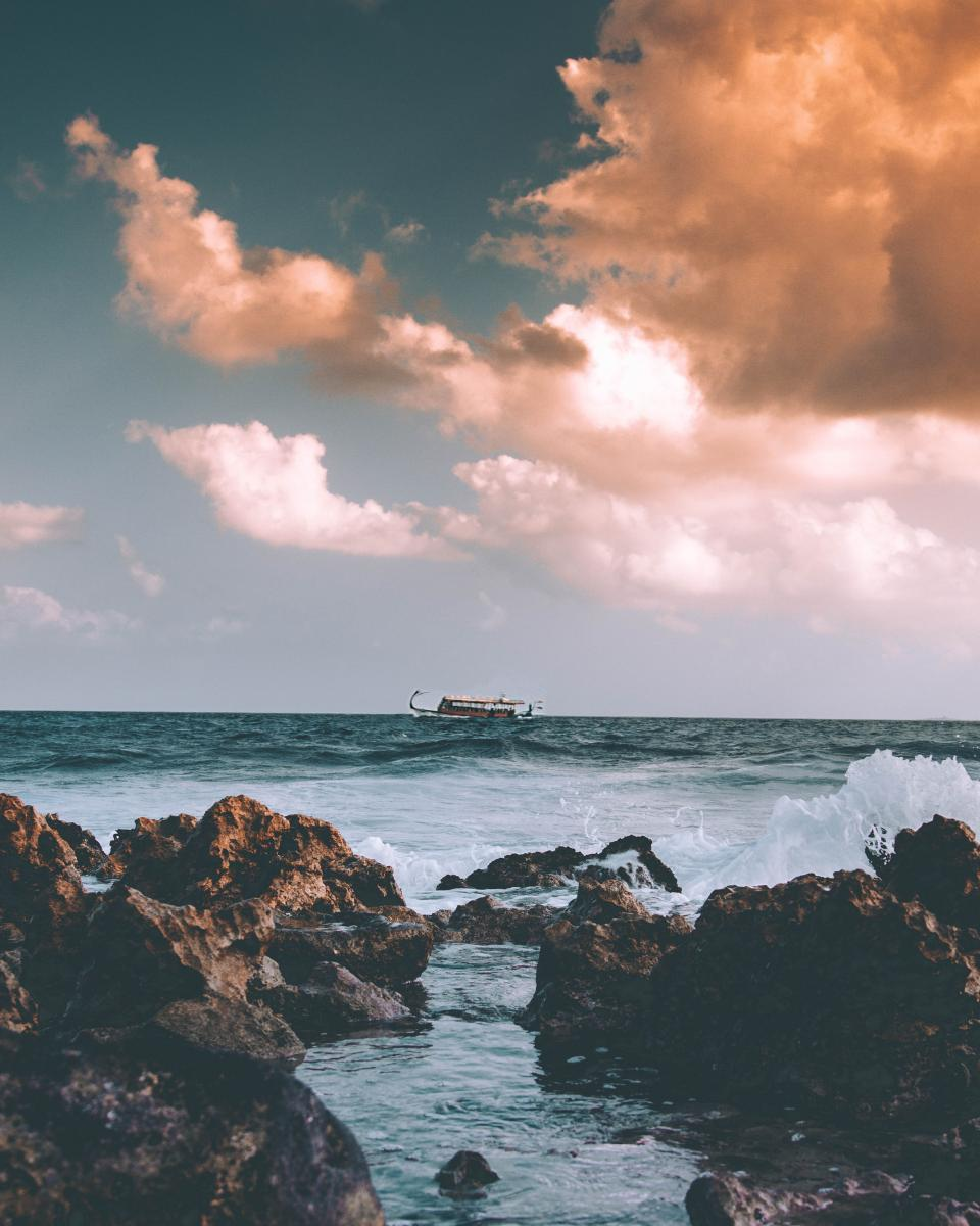 nature water ocean sea beach waves current boat clouds sky rocks travel adventure
