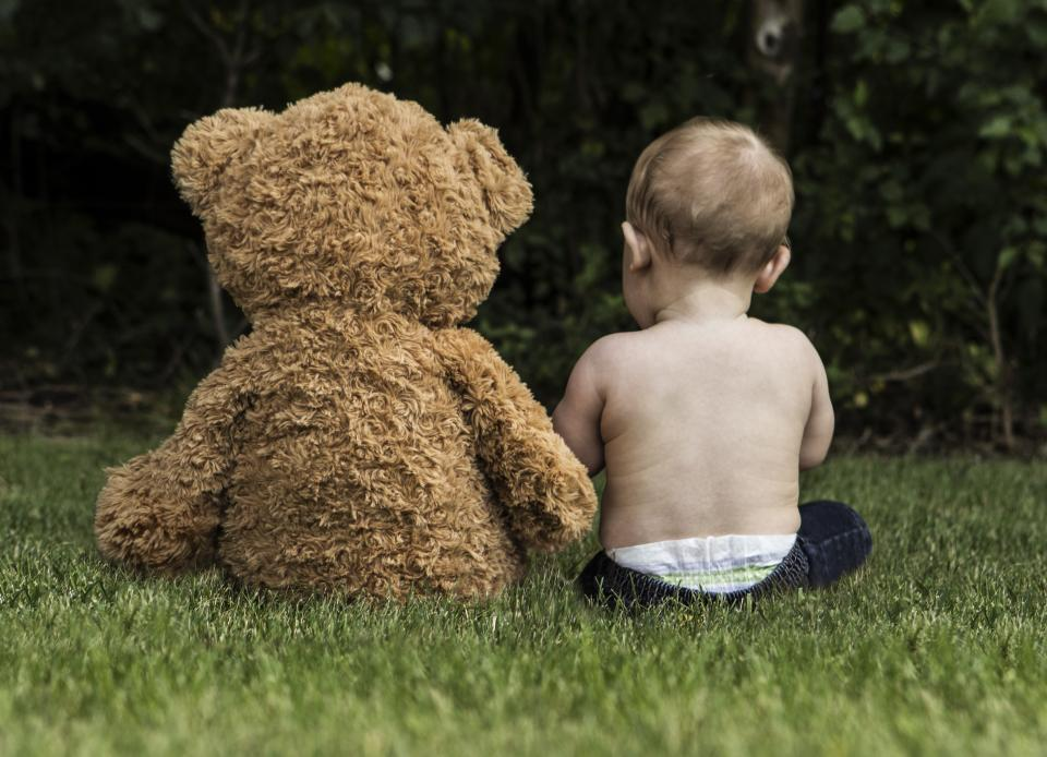 green grass grassland outdoor landscape nature baby kid child toddler playing teddy bear stuffed toy