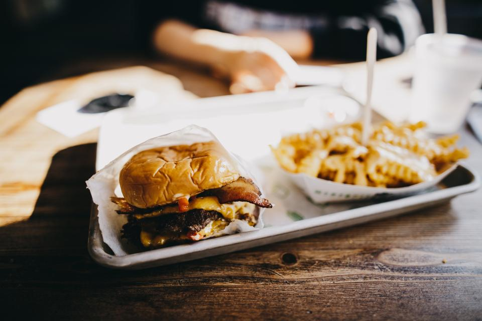 food burger delicious tray meat bun fries potato bacon cheese table wood