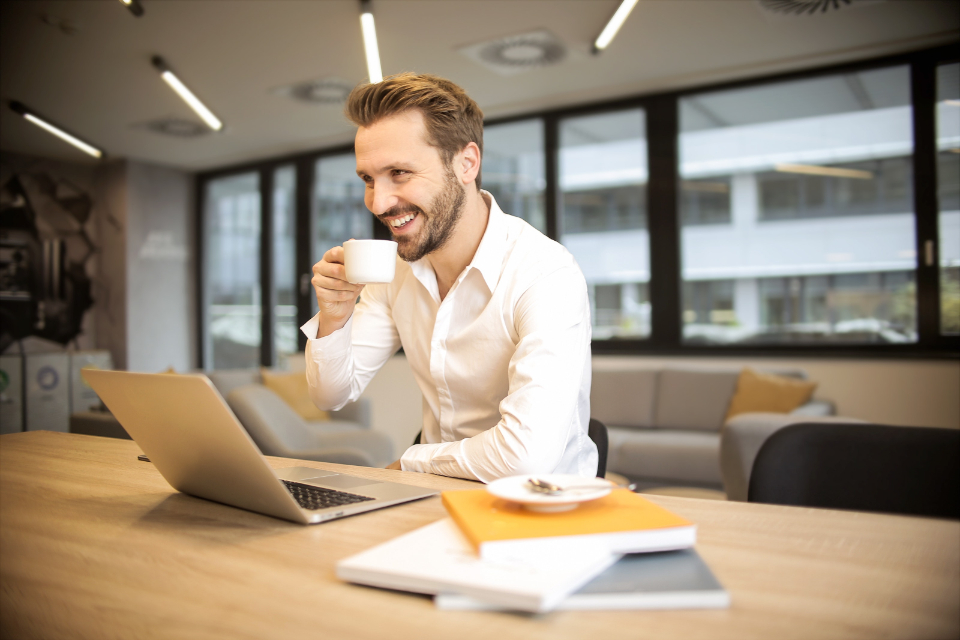 business man smiling coffee cup laptop computer technology desk office work male people