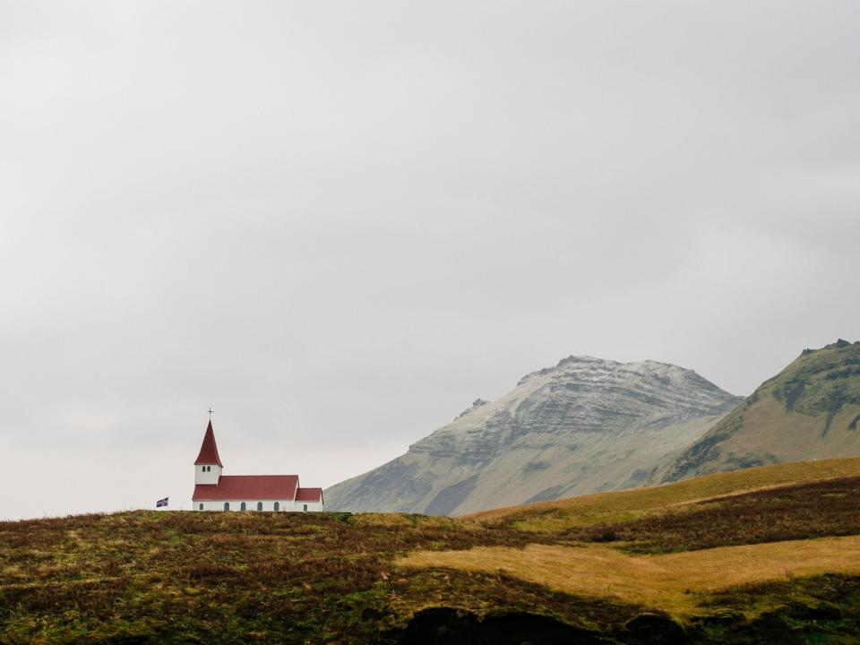 church cross red roof grey sky mountains cliffs hills fields valleys grass dirt outdoors plains flag