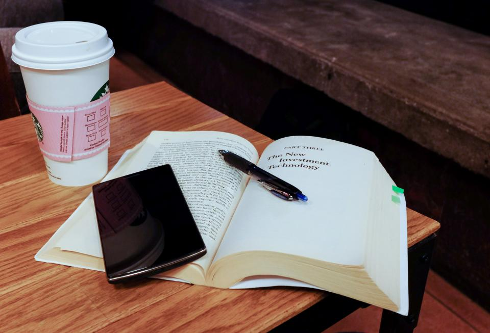 smartphone mobile technology book reading pen Starbucks coffee desk table learning