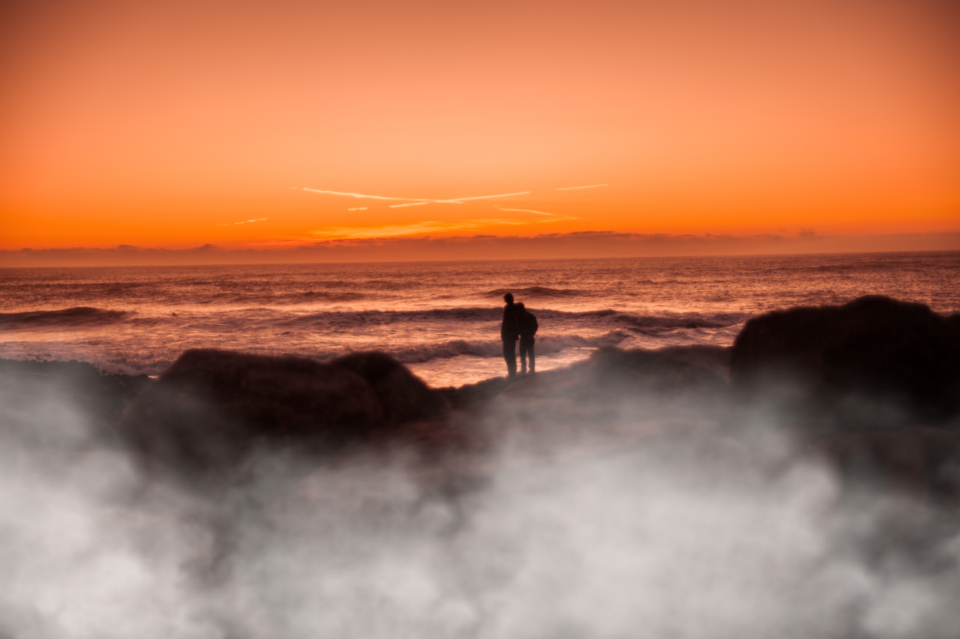 ocean sunset couple people silhouette rocks shore coast sea water waves sunrise mist sky clouds nature outdoors