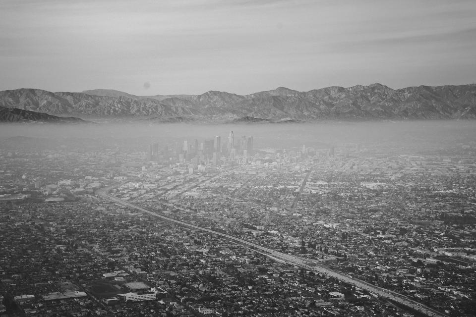 city aerial view buildings architecture mountains landscape sky black and white fog