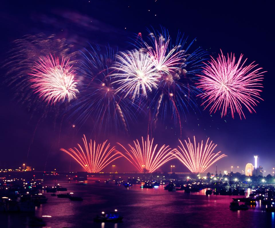 fireworks lights show celebration purple night dark evening sky cityscape buildings water boats urban city