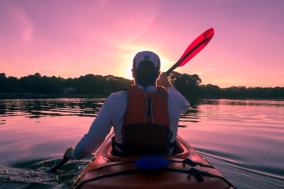 guy man kayaking paddling outdoors lake water fitness nature sunset dusk sky people life jacket hat adventure athlete