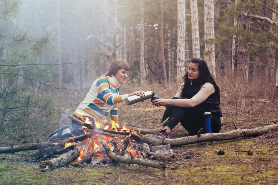 women girls talking smile happy friends sitting trees fire camping travel outdoor drinks firewood forest