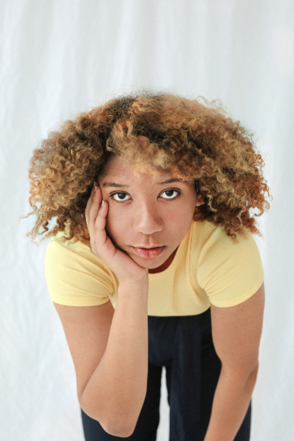woman hand face thought think yellow t-shirt curly hair black eyes