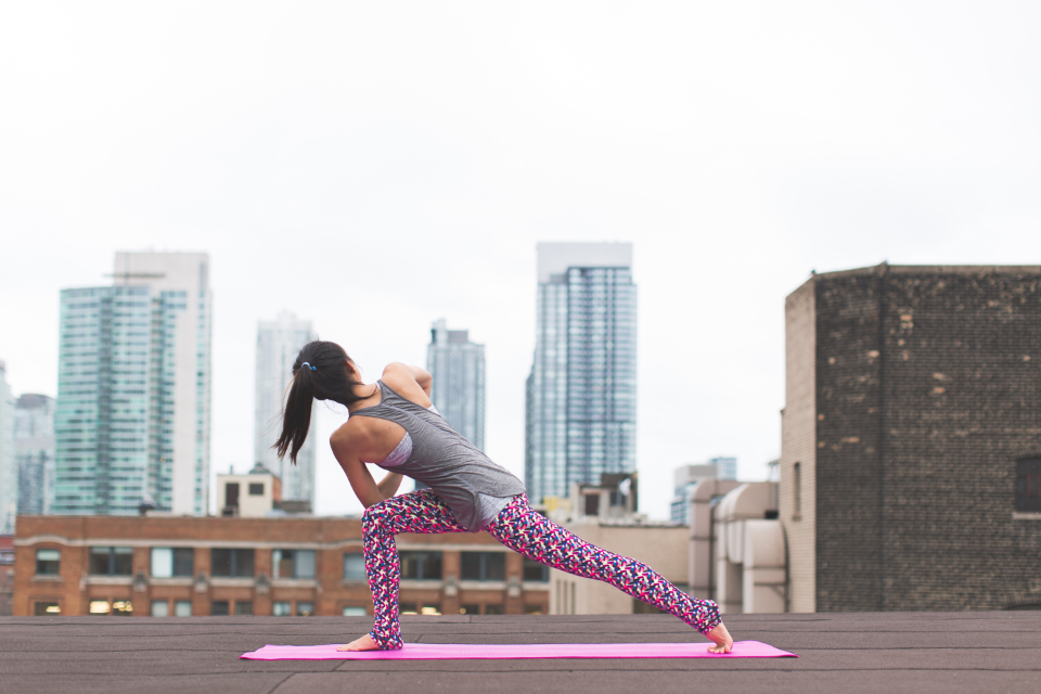 city stretched woman yoga outdoors oriental asian adult architecture buildings city daylight health exercise fit healthy person pose rooftop skyscraper urban sport