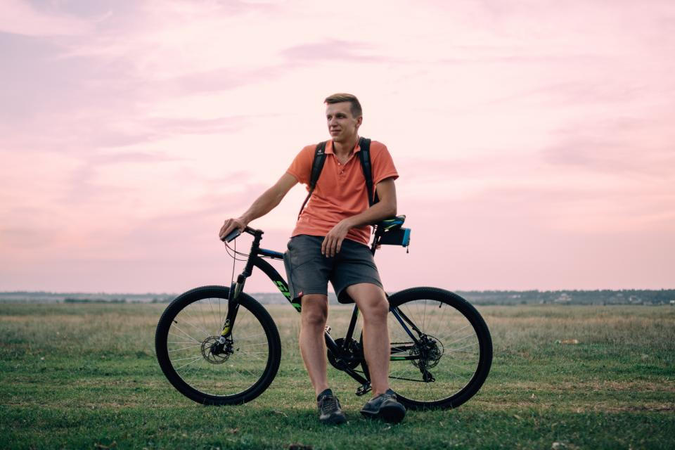 green grass nature outdoor adventure travel clouds sky bike bicycle people man male guy ride