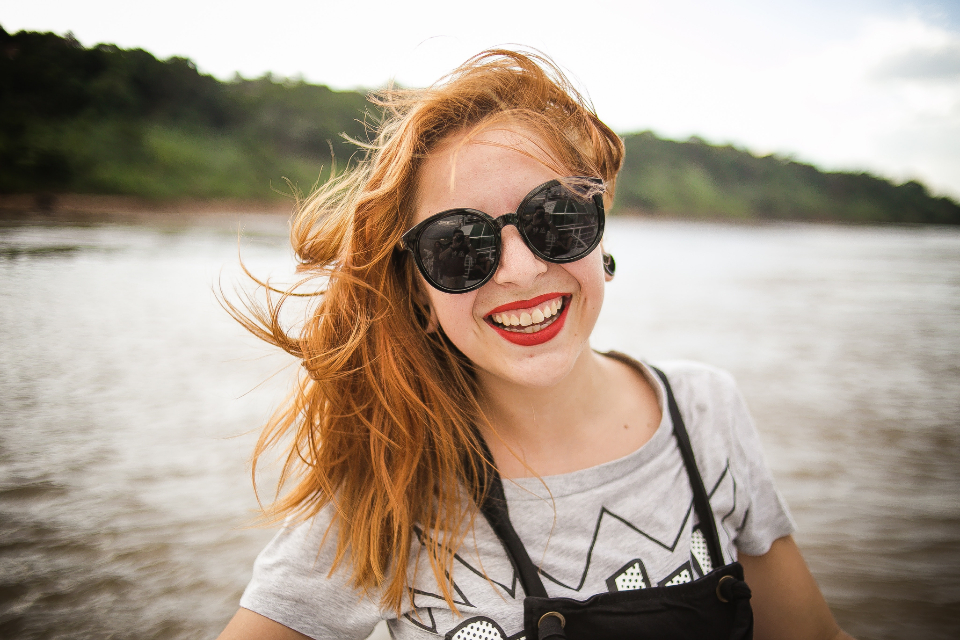 woman sunglasses smiling smile happy red hair windy boat lake river nature lipstick