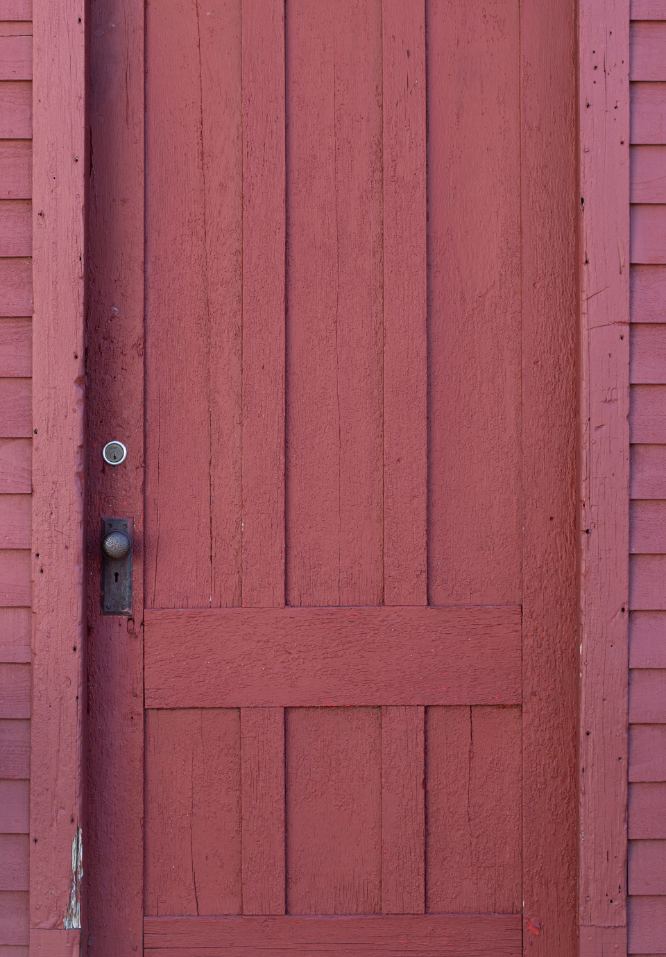 red door wooden building barn rustic entrance exterior old wood painted background design architecture