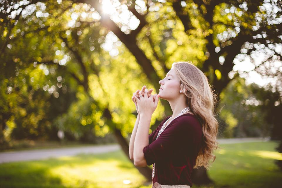 people girl praying nature green trees grass bokeh