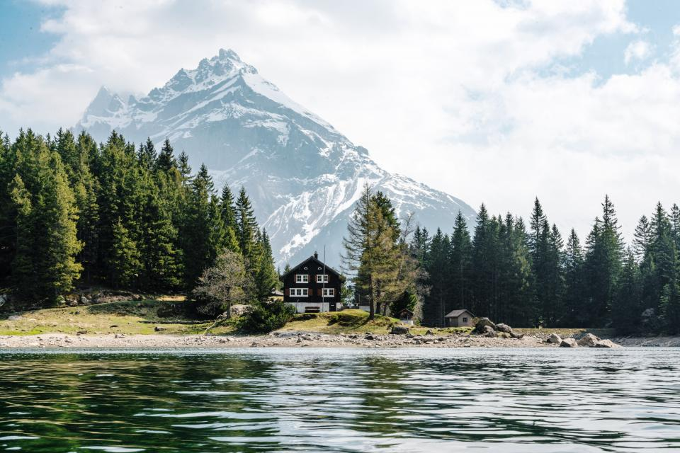 nature landscape mountains summit peaks snow forest trees shore sand rocks grass water lake ripples surface house cottage cabin sky clouds