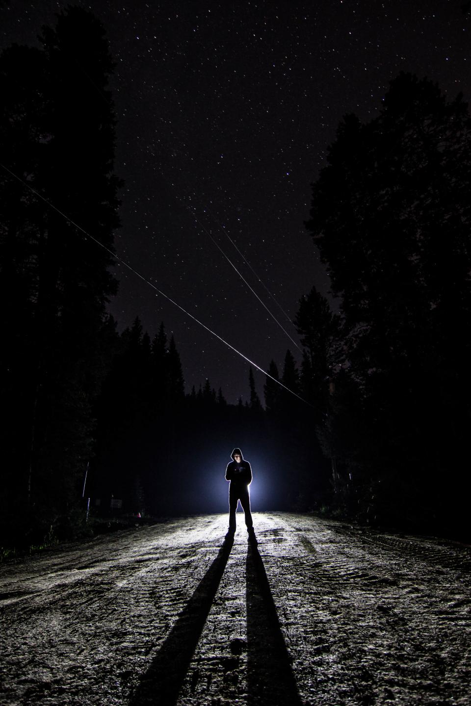 guy man male people stand light shadow silhouette spotlight path road dirt soil trees forests night sky stars constellation falling wish