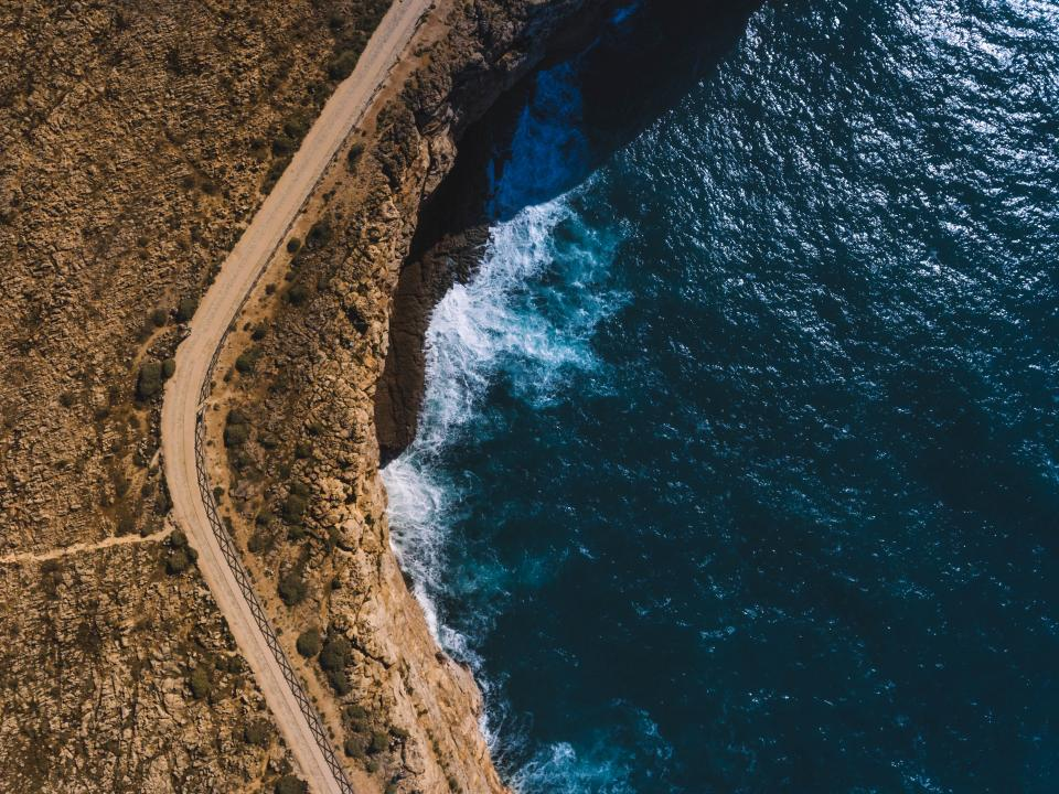 sea ocean blue water waves nature aerial view path road coast rock