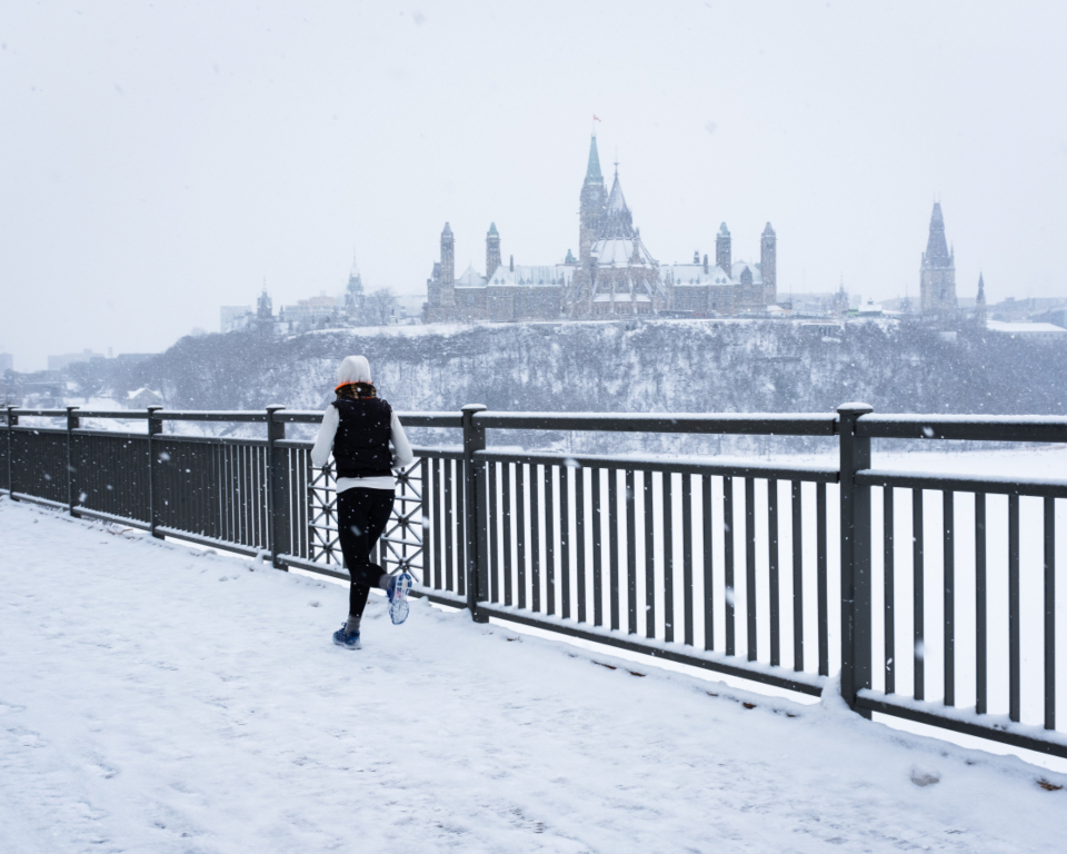 running urban exercise runner snowing female bridge path snow cold river ice city winter woman