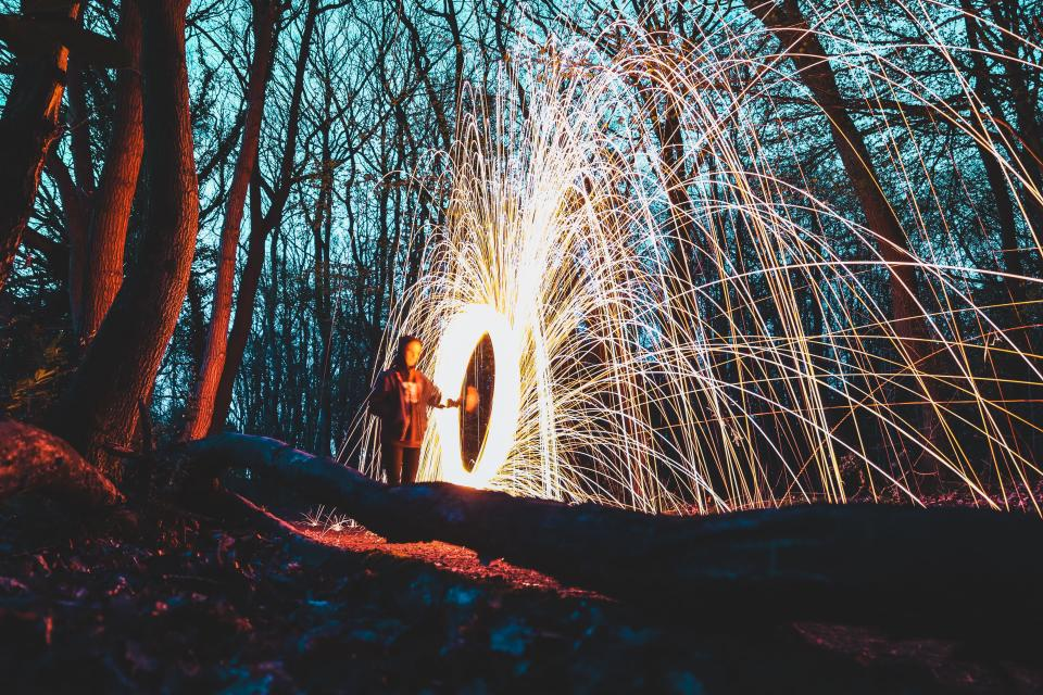 still fireworks light show flames slow shutter exposure bulb photography guy man people night shadows trees plant
