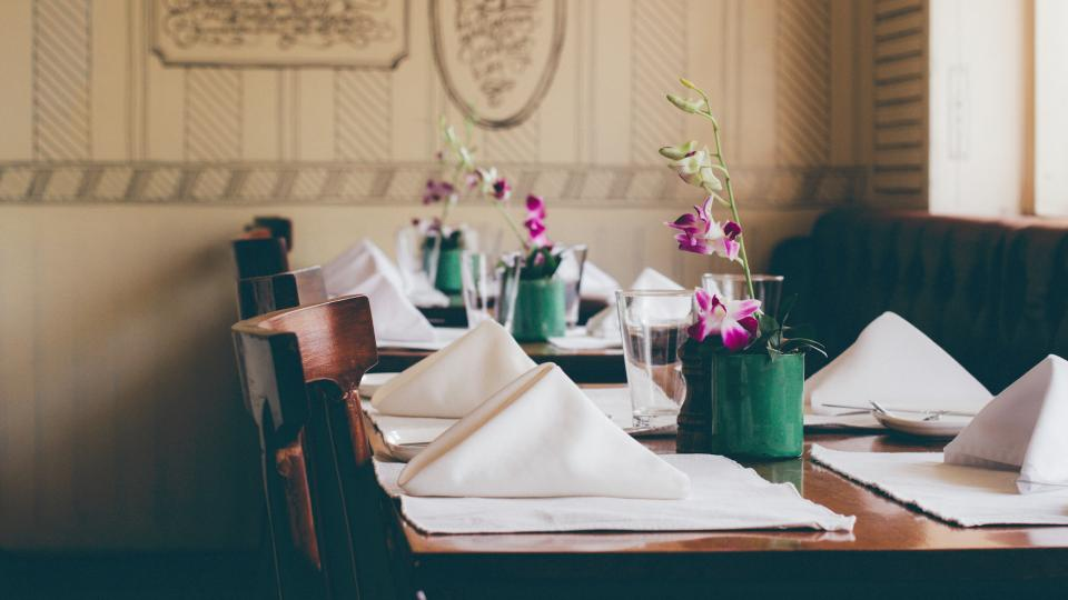 lifestyle food restaurant table napkins glasses vase flowers