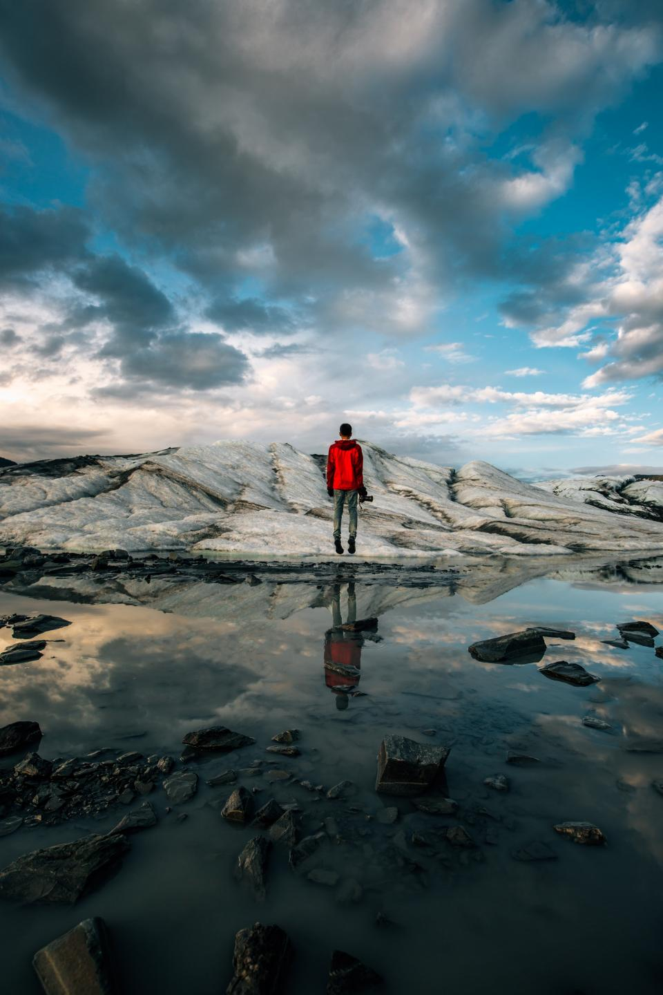 guy man male people back contemplate stand nature landscape rocks slabs water lake puddle reflection sky clouds horizon travel trek photography