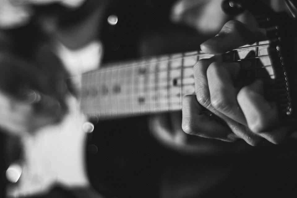 still music instruments guitar fret chords strum strings play guy man people play black and white bokeh