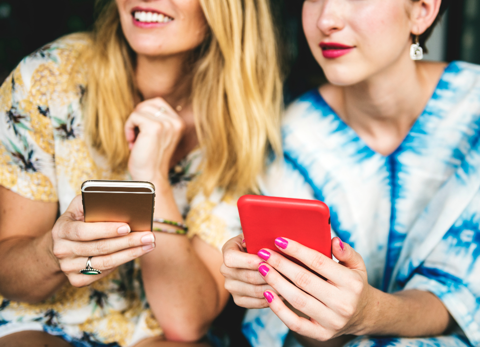 browsing carefree casual caucasian cheerful close-up connection device digital friends friendship girls holidays internet joy leisure looking modern sitting smartphone smiling summer technology together happy girls women people