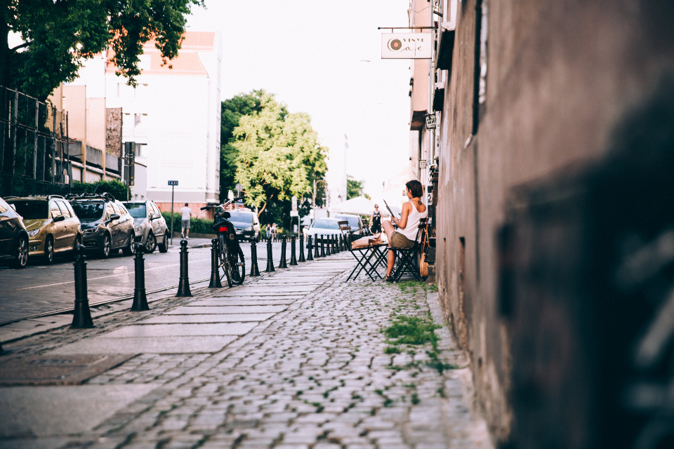 cafe reading newspaper woman sitting casual street outside cobblestone bicycle cars city urban buildings table chair travel