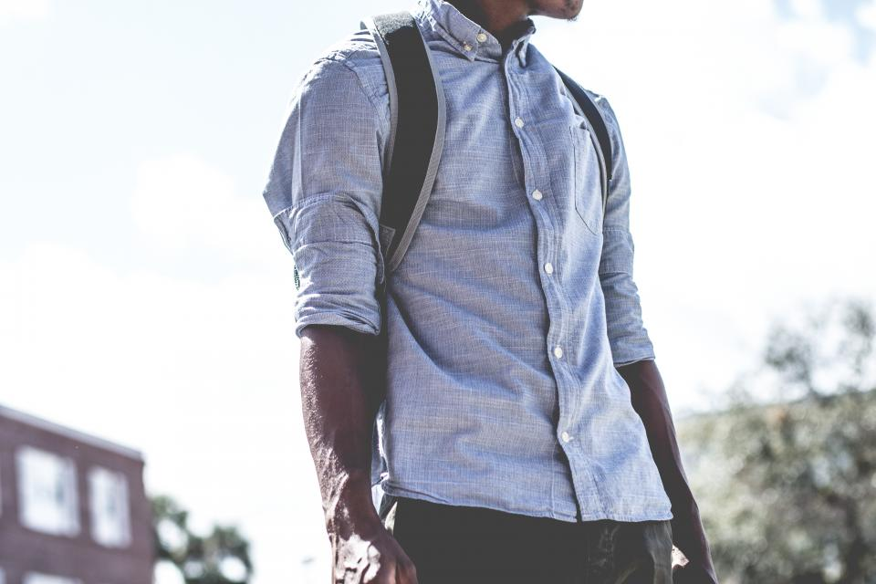 guy man fashion clothing backpack african american bokeh building plants trees street male sunlight clouds
