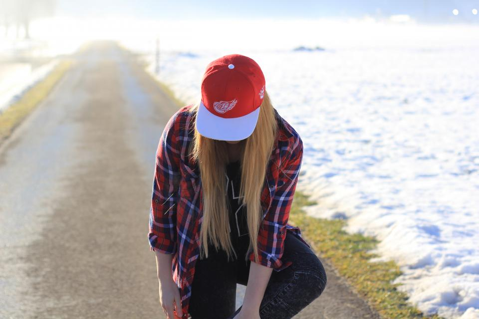 people girl woman lady walking alone street road grass snow winter travel outdoor red cap