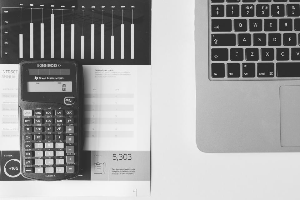 calculator numbers accounting charts graphs finance macbook laptop computer technology business black and white desk