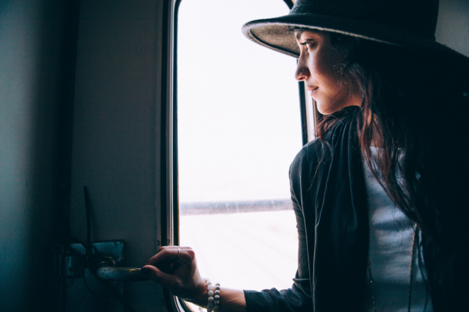 woman looking window person female lady train transport travel hat fashion
