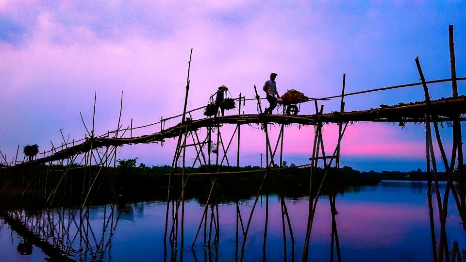 men people work bridge wood stilts support water reflection sky horizon clouds blue pink