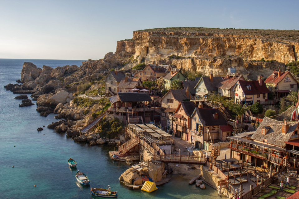 popeye village mediteranean sea Malta Cliffs rock face rock stone sea ocean blue sky boats houses wood