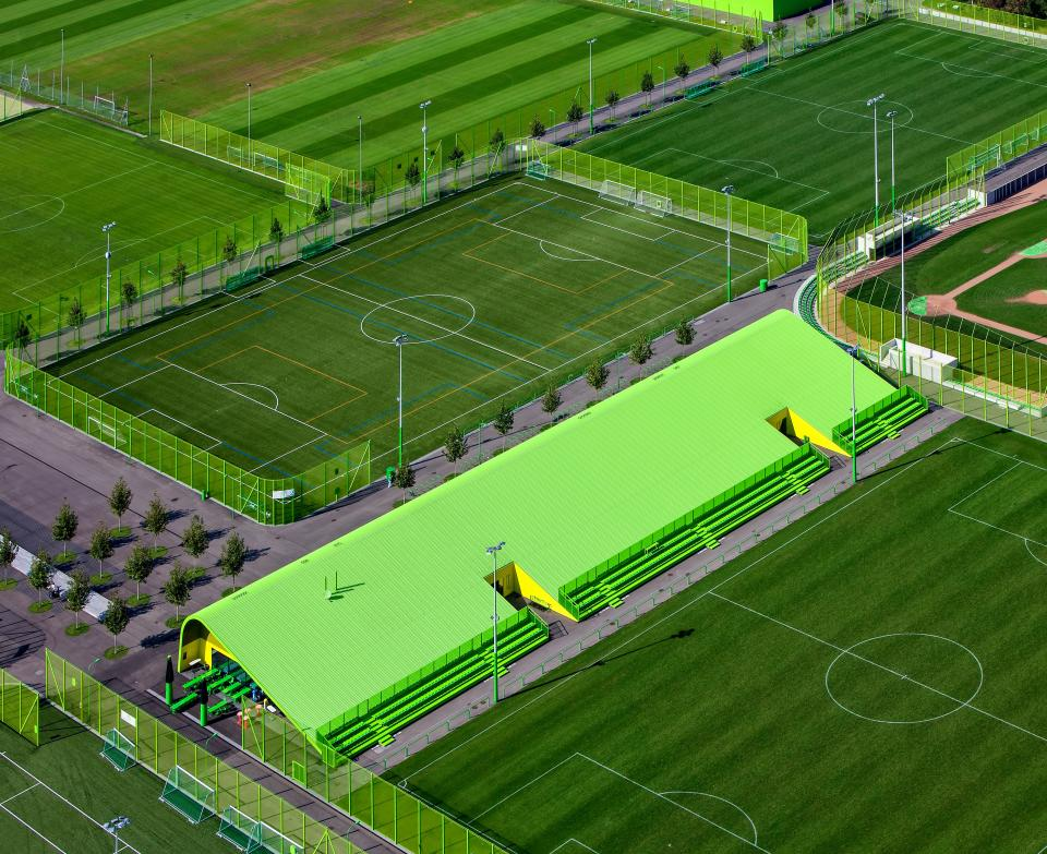 green field sport venue game tournament fence aerial view tree building roof outdoor